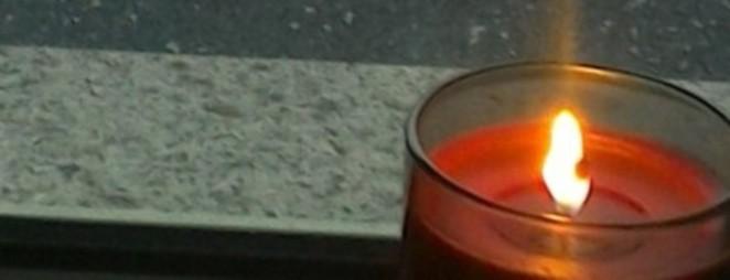 Eine brennende Kerze vor der Balkontür